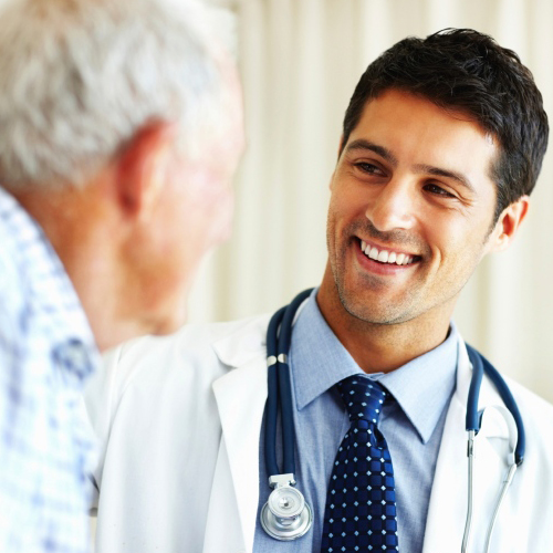 Young Male Doctor Smiles At Older Male Patient With IPF
