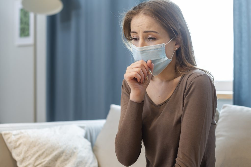 Woman sitting on sofa with mask on and coughing from long COVID